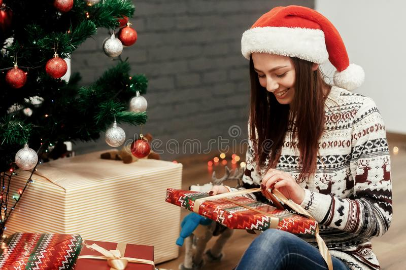 Beautiful happy emotional woman in red santa hat and reindeer sw. Eater smiling after receiving christmas presents near decorated christmas tree, greeting card stock photos