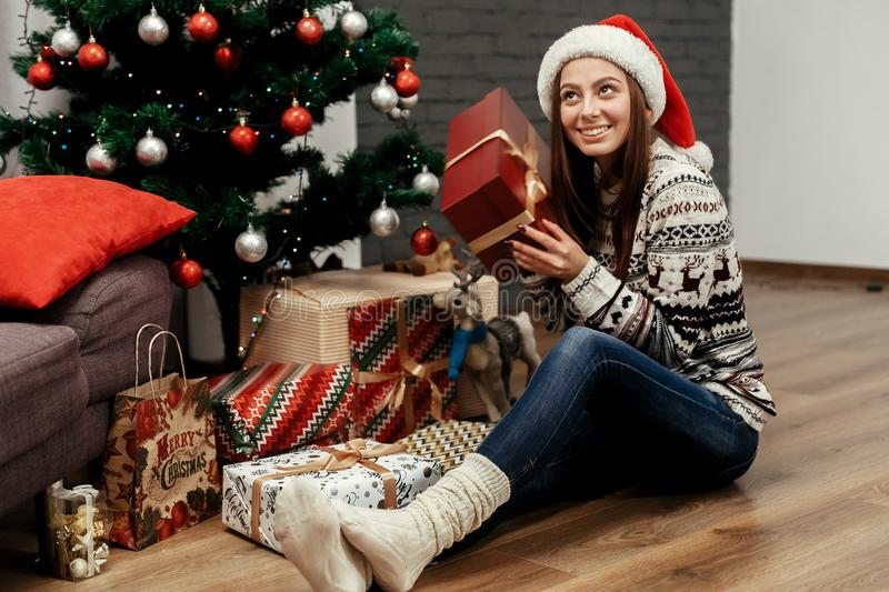 Beautiful happy emotional woman in red santa hat and reindeer sw. Eater smiling after receiving christmas presents near decorated christmas tree, greeting card royalty free stock photos