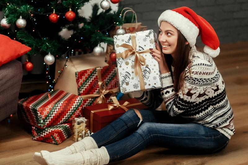 Beautiful happy emotional woman in red santa hat and reindeer sw. Eater smiling after receiving christmas presents near decorated christmas tree, greeting card royalty free stock photography