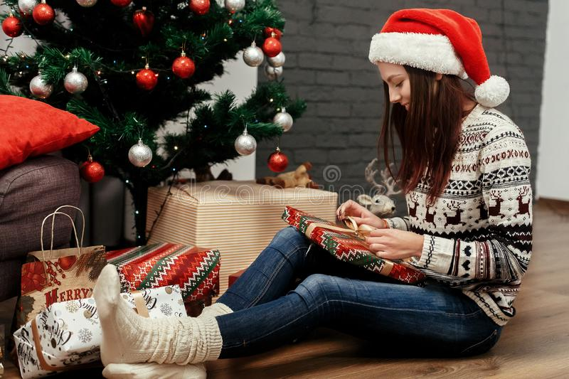 Beautiful happy emotional woman in red santa hat and reindeer sw. Eater smiling after receiving christmas presents near decorated christmas tree, greeting card royalty free stock photo
