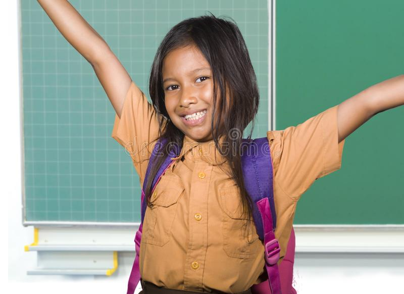 Beautiful happy and excited female child in school uniform carrying student bag smiling cheerful standing at classroom blackboard. Portrait of beautiful happy stock photography