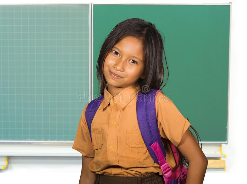 Beautiful happy and excited female child in school uniform carrying student bag smiling cheerful standing at classroom blackboard. Portrait of beautiful happy stock images