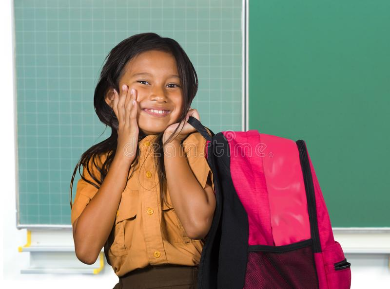 Beautiful happy and excited female child in school uniform carrying student bag smiling cheerful standing at classroom blackboard. Portrait of beautiful happy stock image