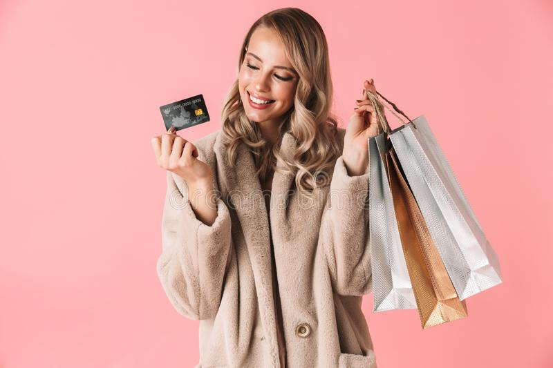 Beautiful happy excited young pretty woman posing isolated over pink wall background holding shopping bags and credit card royalty free stock image