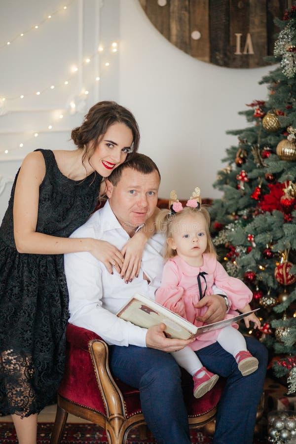 Beautiful happy family with baby girl near Christmas tree royalty free stock photo