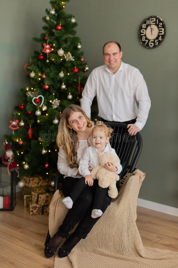 Beautiful happy family at the New Year tree. royalty free stock image