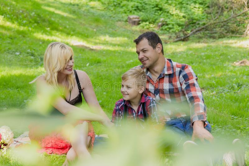Beautiful happy family resting on a picnic on a sunny day. Beautiful happy family resting on a picnic on a sunny day royalty free stock images