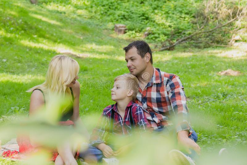Beautiful happy family resting on a picnic on a sunny day. Beautiful happy family resting on a picnic on a sunny day royalty free stock photo