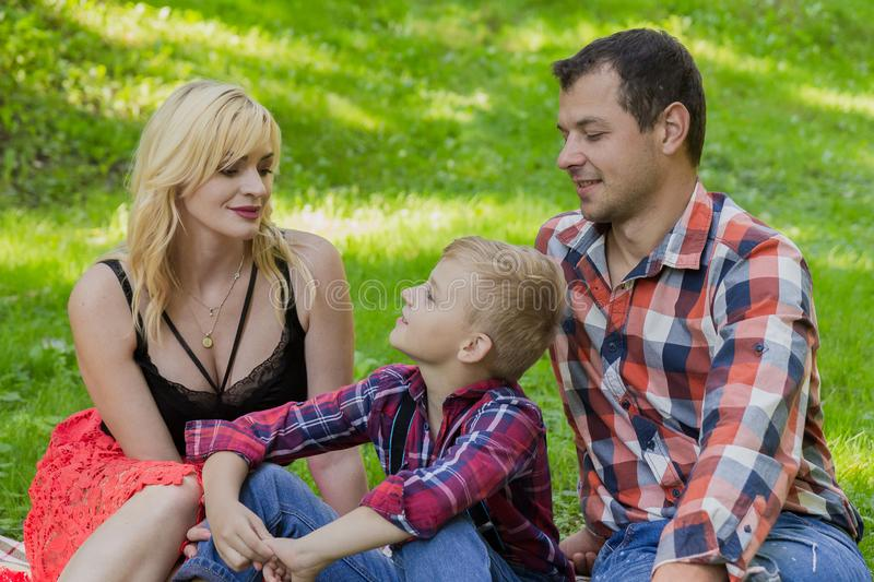 Beautiful happy family resting on a picnic on a sunny day. Beautiful happy family resting on a picnic on a sunny day royalty free stock photos