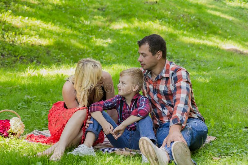 Beautiful happy family resting on a picnic on a sunny day. Beautiful happy family resting on a picnic on a sunny day stock photo
