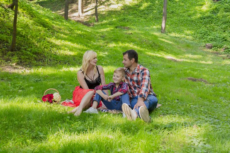 Beautiful happy family resting on a picnic on a sunny day. Beautiful happy family resting on a picnic on a sunny day royalty free stock image
