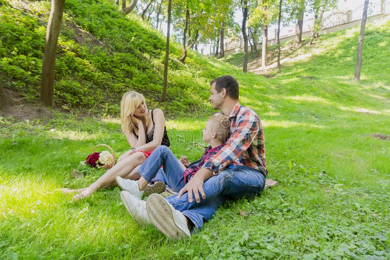 Beautiful happy family resting on a picnic on a sunny day. Beautiful happy family resting on a picnic on a sunny day royalty free stock photography
