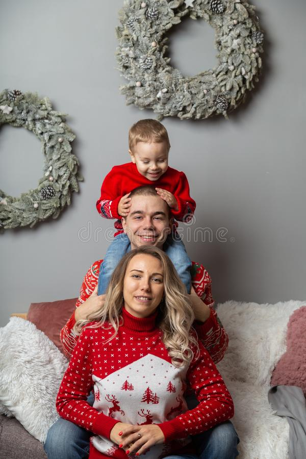 Beautiful happy family of three in a New Year`s decor. Happy Merry Christmas 2020. Beautiful happy family of three in a New Year`s decor. Happy Merry Christmas stock images
