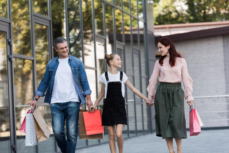 Shooping. Beautiful happy family walking with shooping bags royalty free stock photography