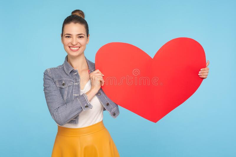 Beautiful happy fashionably dressed woman with amiable smile holding big red paper heart, expressing love affection. Symbol of charity and kindness. indoor stock photos