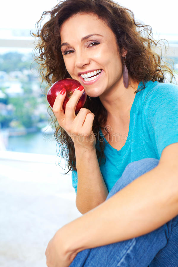 Beautiful happy female eating an apple royalty free stock image