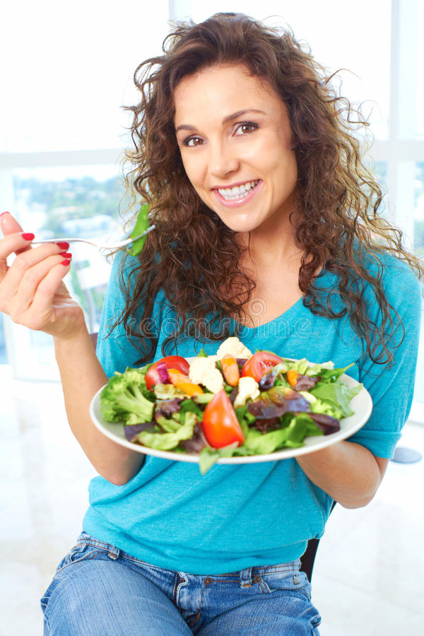 Beautiful happy female eating a salad royalty free stock photo
