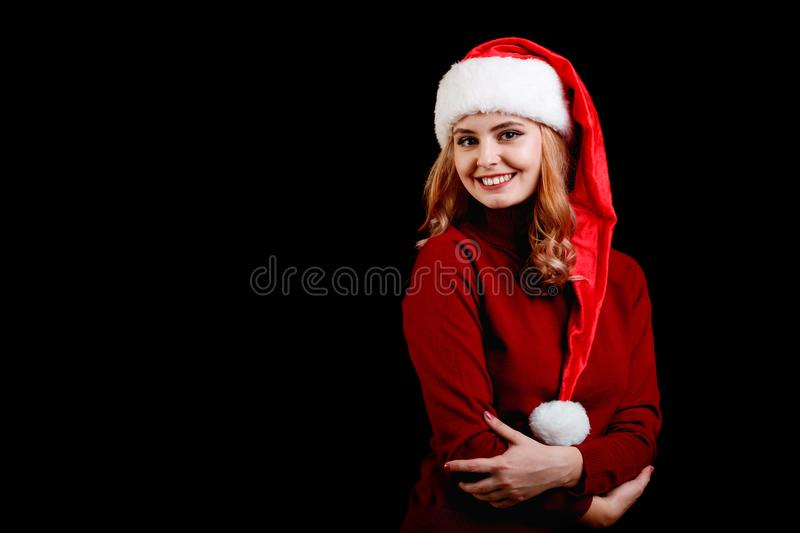 Beautiful happy festive girl in a santa cap on a black background. Christmas costume concept. Copy space. royalty free stock photography