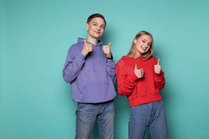 Beautiful happy friends boy and girl in casual clothes showing thumbs up and looking at the camera stock photography