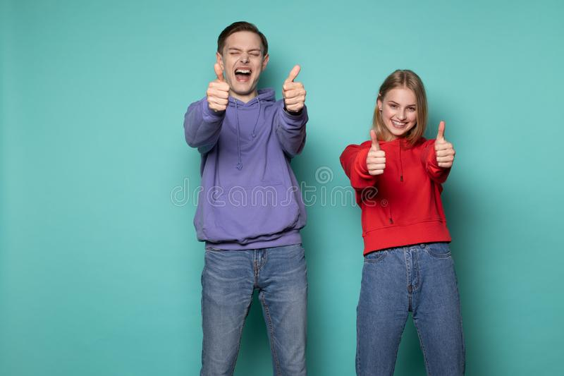 Beautiful happy friends boy and girl in casual clothes showing thumbs up and looking at the camera royalty free stock photo