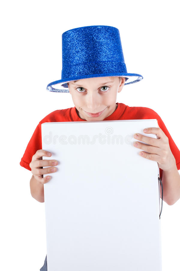 Beautiful happy funny child wearing blue party hat holds a rectangular white banner. Beautiful happy funny child wearing blue party hat holds a rectangular white royalty free stock image