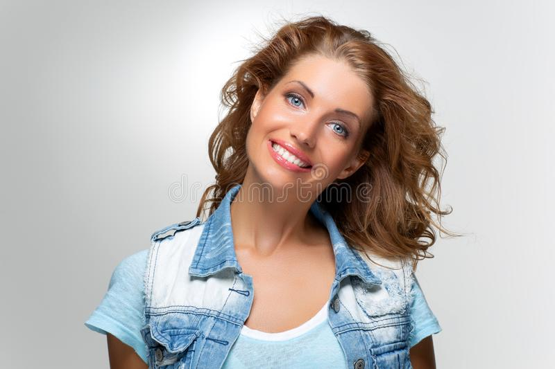 Beautiful happy girl in blue jeans jacket stock image