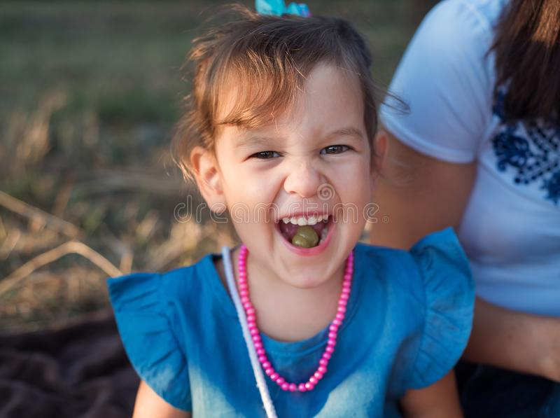 A beautiful and happy girl eats grapes. Happy Children `s portrait stock photography
