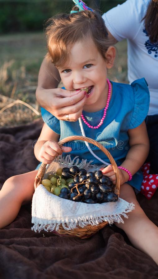 A beautiful and happy girl eats grapes. Mom feeds the baby at a family picnic royalty free stock image