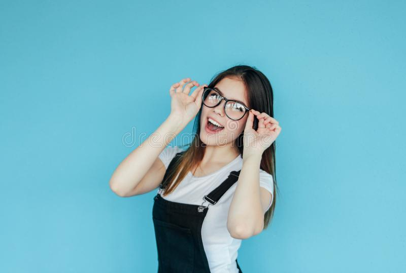 Beautiful happy girl in glasses with dark long hair in white t-shirt isolated on blue background royalty free stock image