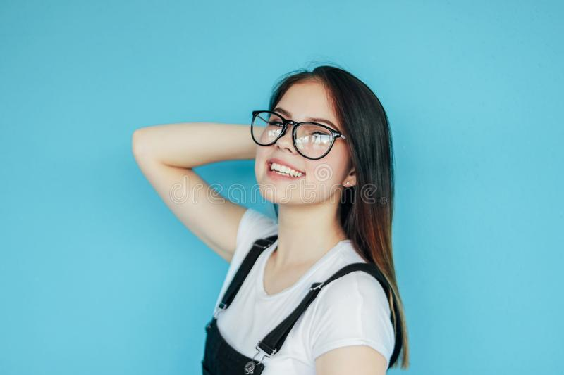Beautiful happy girl in glasses with dark long hair in white t-shirt isolated on blue background royalty free stock photos