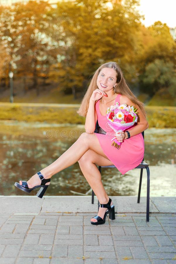 Beautiful happy girl in pink dress with flowers and balls sitting on chair in park near pond in autum stock image