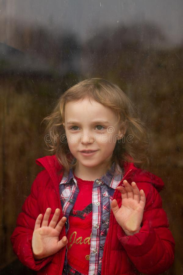 Beautiful happy girl in a red jacket looks through the raining glass window stock photography