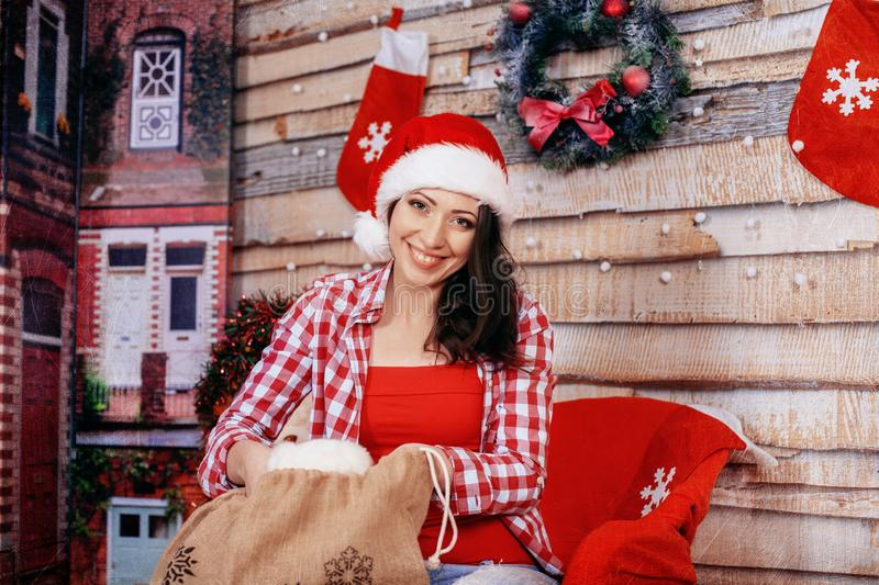 Beautiful happy girl in red shirt gets gifts from the bag. The c royalty free stock photos