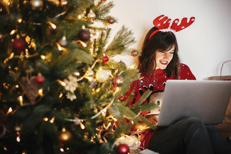 Beautiful happy girl in reindeer antlers sitting with laptop at. Golden beautiful christmas tree with lights and presents in festive room. christmas shoppoing royalty free stock photo