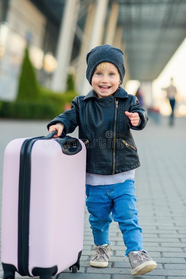 Beautiful happy girl travels with stylish suitcase. Little child traveler goes to the trip from airport. royalty free stock image