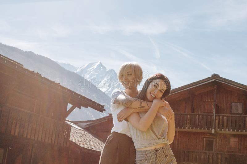 beautiful happy girls hugging while standing between wooden houses in mountain village mont royalty free stock photos