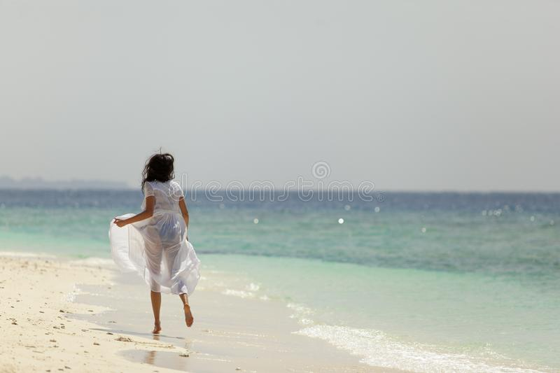 Girl running along the beach coast stock images
