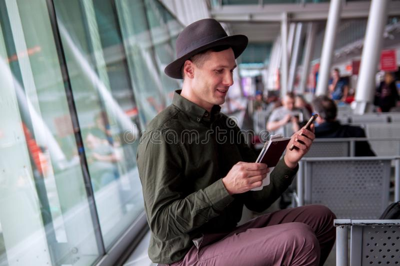 A beautiful happy guy in a hat and shirt talking on the phone and smiling at the airport royalty free stock photography