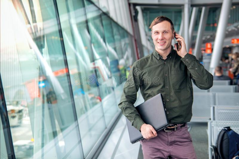 A beautiful happy guy with a laptop and shirt talking on the phone and smiling behind the window at the airport royalty free stock photo