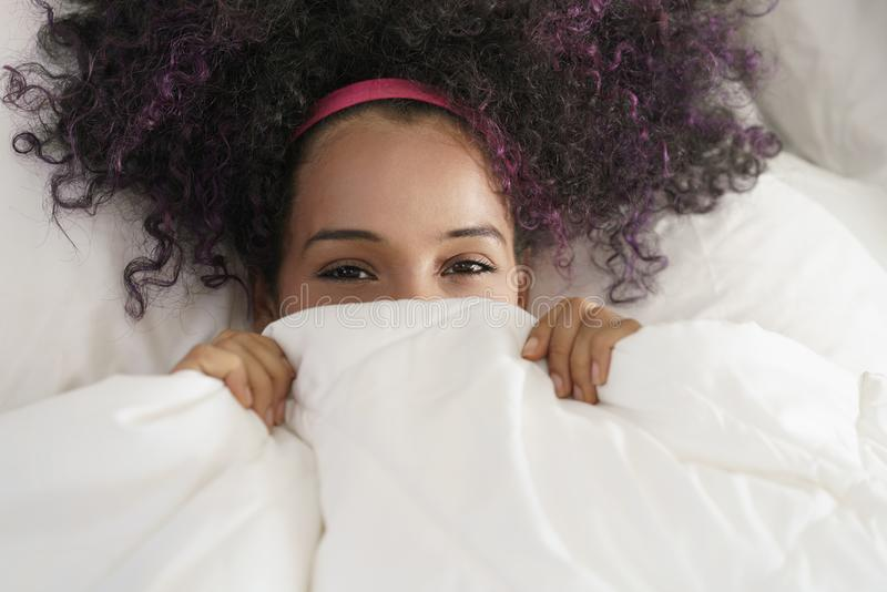 Beautiful Happy Hispanic Teen Waking Up And Smiling Undercover. Portrait of happy black girl looking at camera undercover. Young African American woman waking up stock image