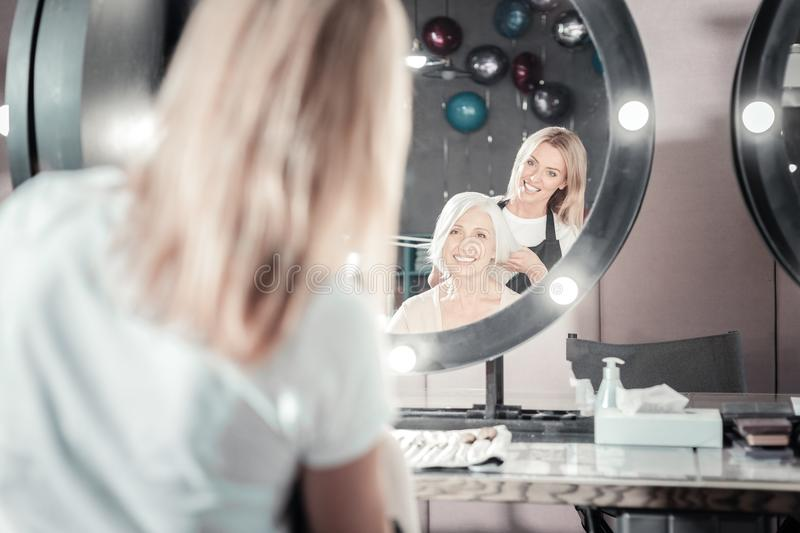 Happy elderly woman looking into the mirror stock image