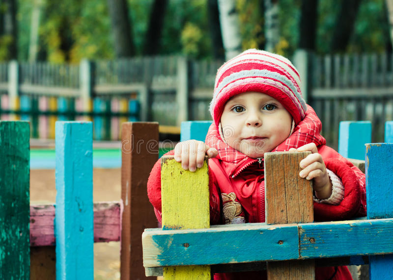 Beautiful happy kid in the red jacket. In the outdoors royalty free stock image