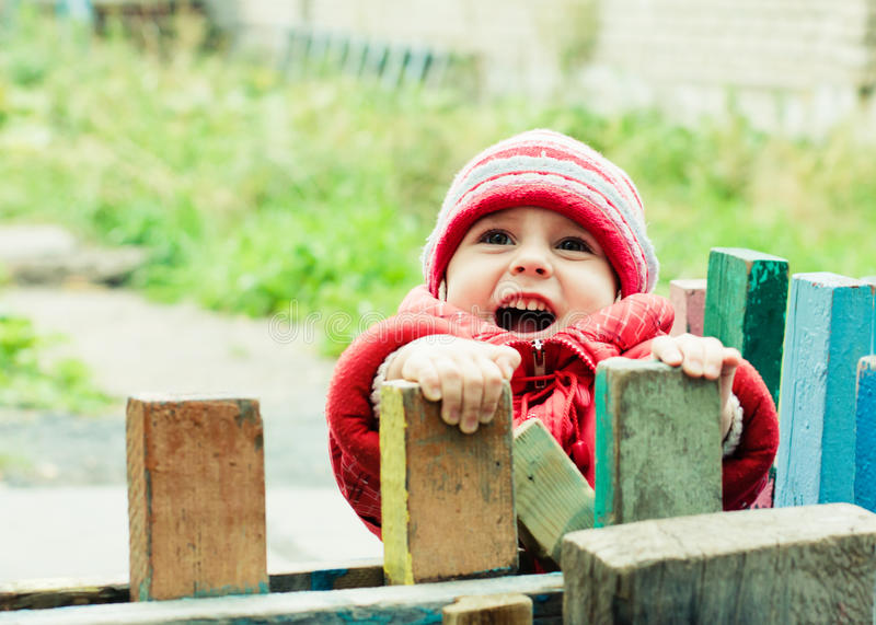 Beautiful happy kid in the red jacket. In the outdoors stock photos