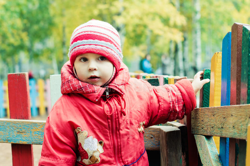 Beautiful happy kid in the red jacket. In the outdoors stock image