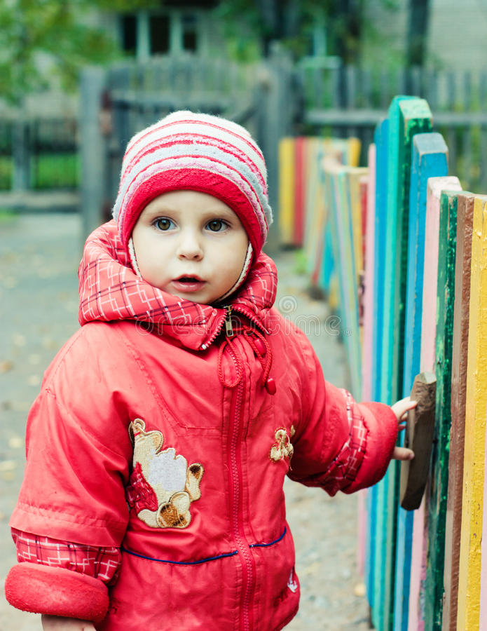 Beautiful happy kid in the red jacket. In the outdoors royalty free stock photo
