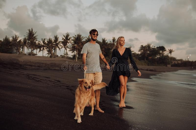 Beautiful happy laugh young hipster couple with golden retriever on beach. ocean an sand. waves. concepte of freedom and stock photos