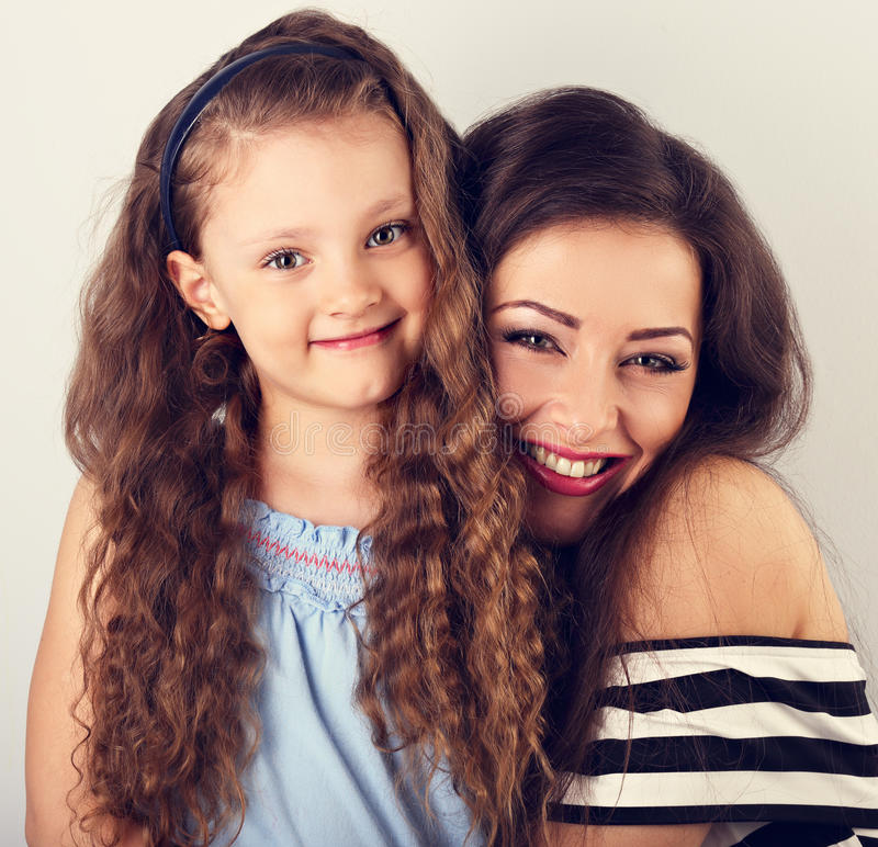 Beautiful happy laughing mother and cute long curly style daughter hugging on blue background. Closeup toned vintage portrait stock photography