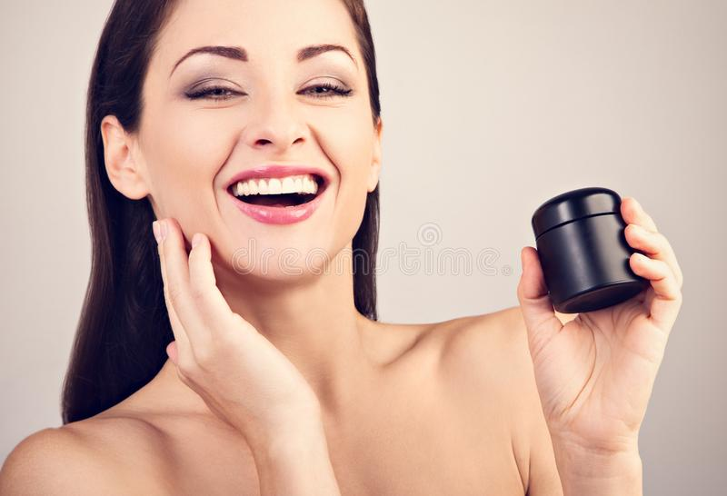 Beautiful happy laughing woman holding jar of skin cream. Smiling female model applying skincare moisturizer the hand on face and royalty free stock photography