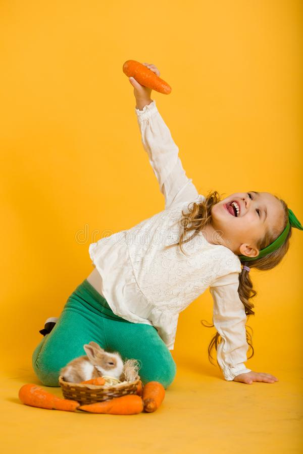 Pretty happy child girl with carrots and her friend little colorful rabbit, Easter holiday concept. Beautiful happy little child girl on Easter holiday with stock image