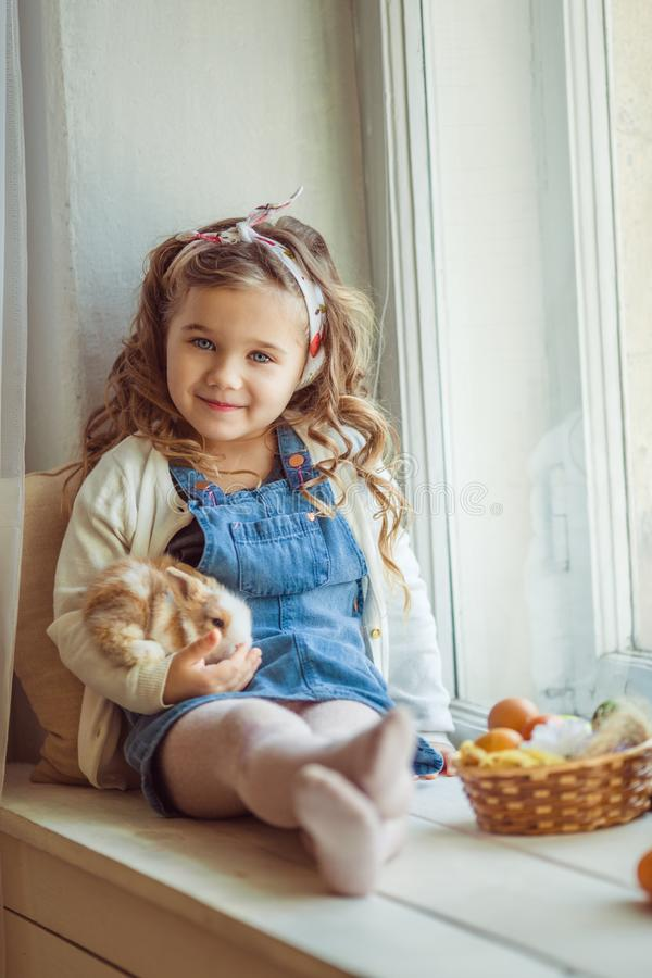 Pretty happy child girl is sitting on window sill with her friend little colorful rabbit, Easter holiday concept. Beautiful happy little child girl is wearing stock photos